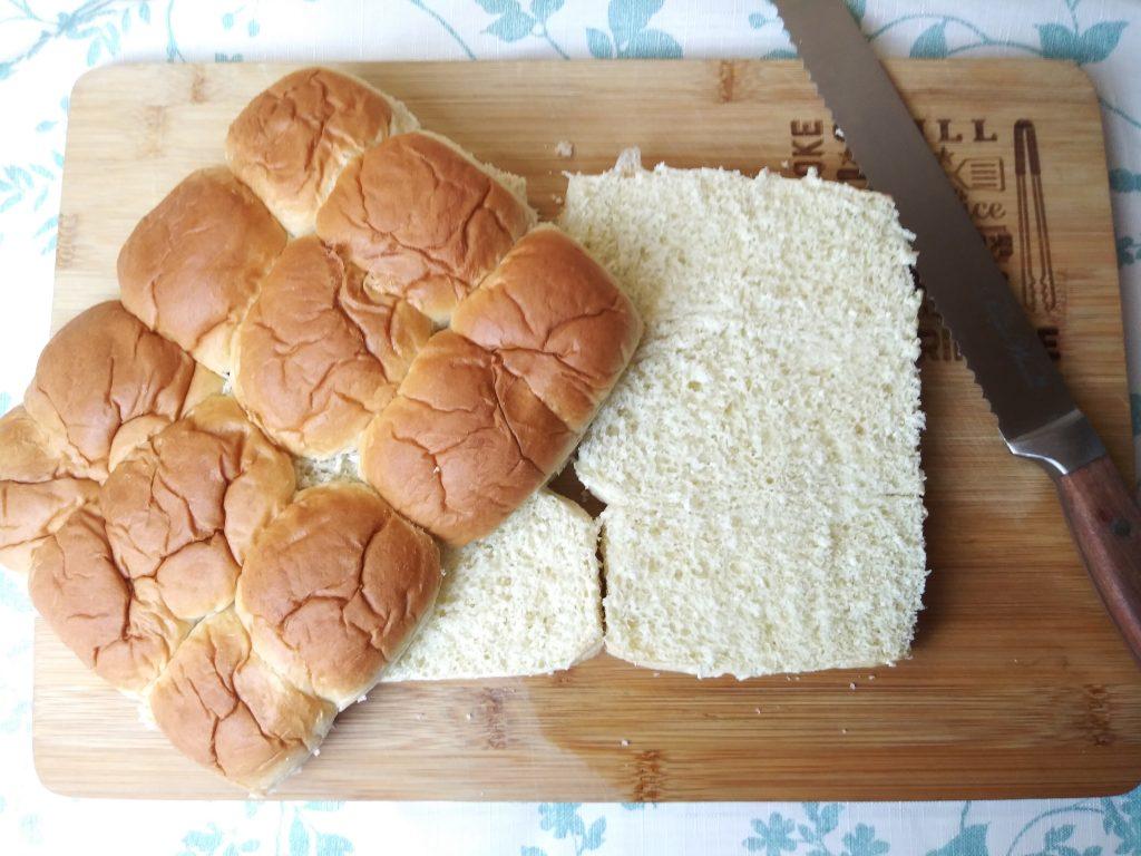 Hawaiian rolls with knife laying on wood cutting board
