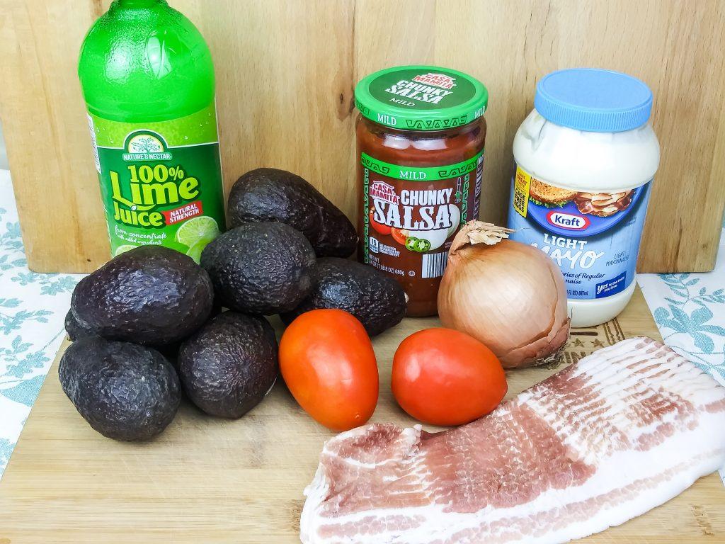 guacamole ingredients sitting on wood cutting board