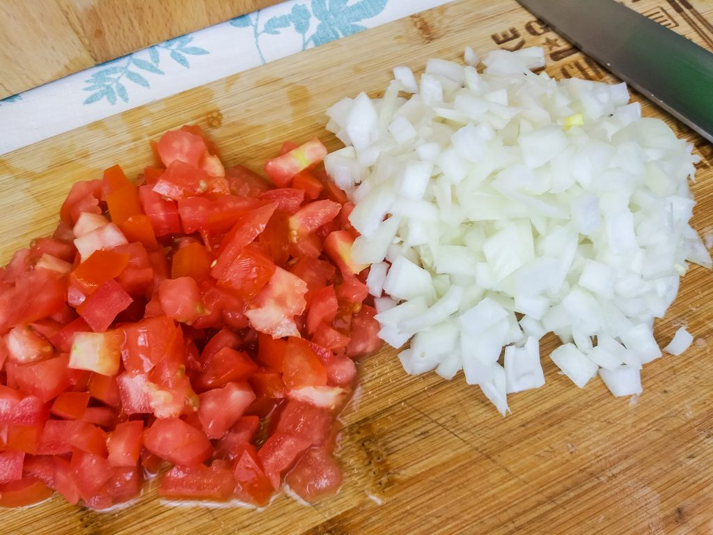 diced tomatoes and onion on a wood cutting board