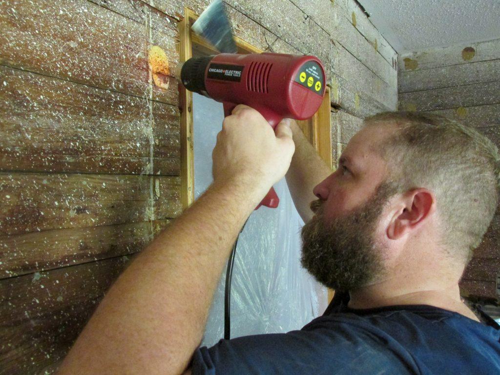 man with beard using heat gun to prep exposed shiplap