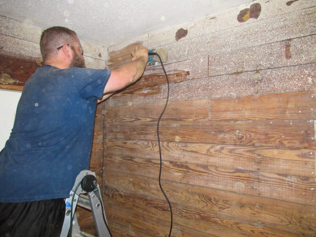 man in blue shirt sanding and prepping exposed shiplap wall