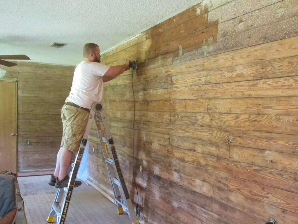 man in white standing on ladder sanding to prep exposed shiplap wall