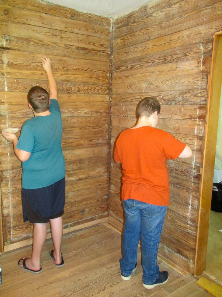 two boys filling nail holes to prep exposed shiplap wall