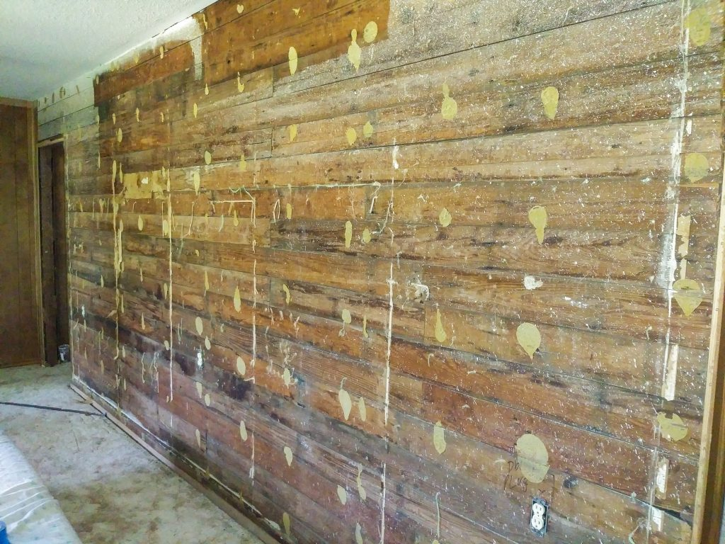 exposed shiplap behind panel wall with glue and cheese cloth