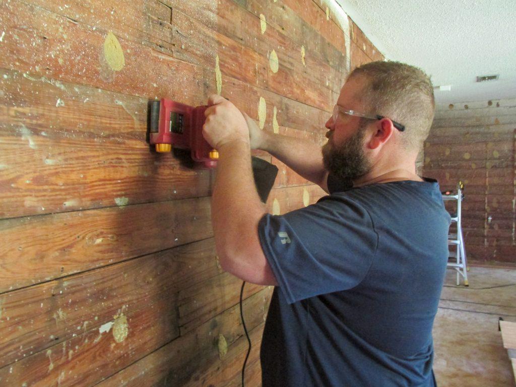 man in blue shirt using belt sander to prep exposed shiplap wall
