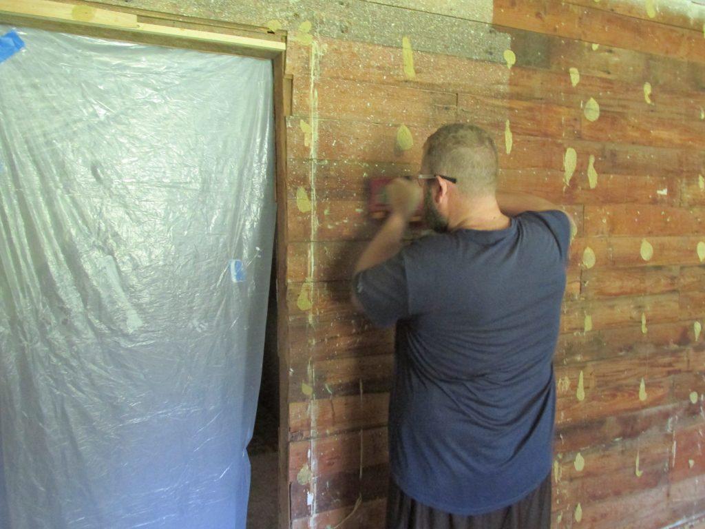 Man sanding with belt sander to prep exposed shiplap