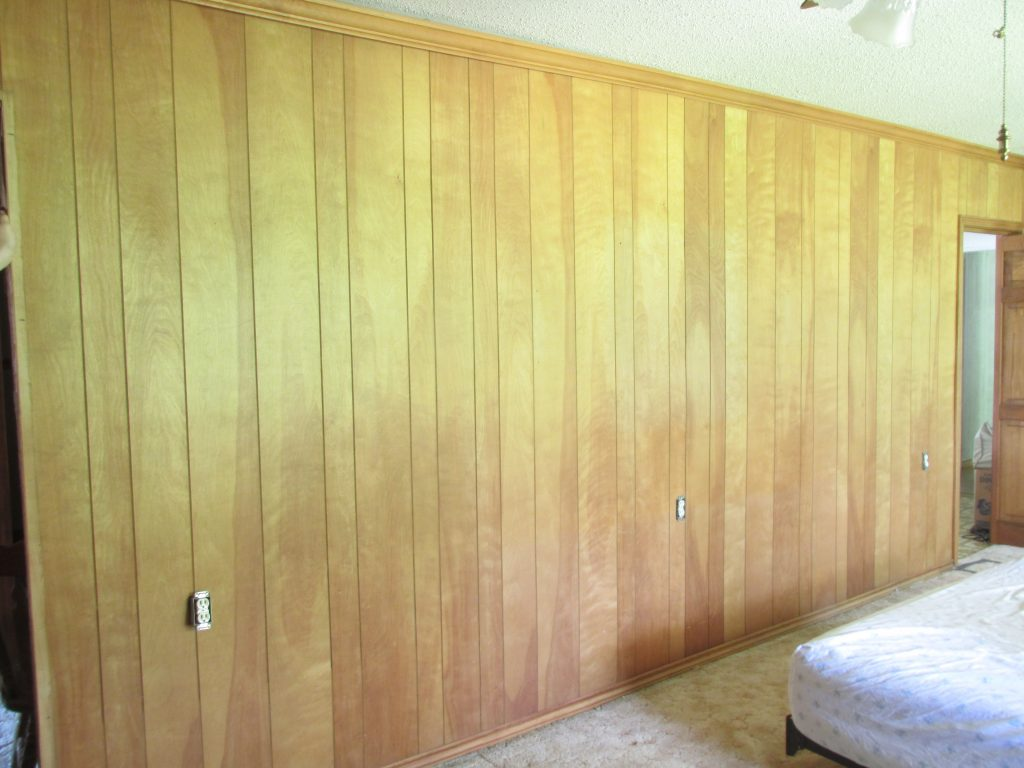 wood panel wall before exposing and prepping shiplap