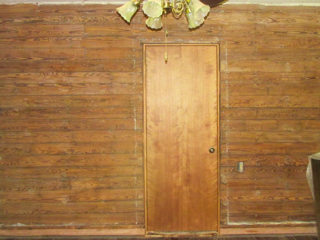 exposed and prepped shiplap wall with wood door in the center of it